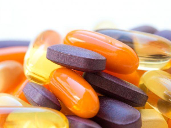 Vitamine und gesunde Ergänzungen auf weißem Hintergrund.