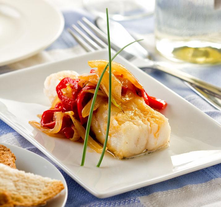 Bacalao oder Kabeljau, serviert mit Paprika-Zwiebeln und Knoblauch.